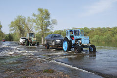 Floods, it flooded road tractor carries cars. Royalty Free Stock Photo