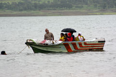 Floods Rescue. A rescue worker pulling a boat of tourists stranded across a flooded river in India Stock Photos