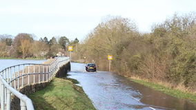 Floods in United Kingdom. A village road is flooded by a river bursting it's banks. A car driving through the flood. This is in the village of Harrold, England stock footage