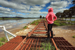 Floodwaters run under buckled train tracks Stock Photos