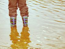 Floody river. Brown water of rised river. Child in rubber boots stock image