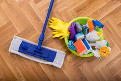 Floor cleaning supplies and equipment. Top view of mopping stick and washbasin full of cleaning supplies and equipment on the parquet Stock Photos