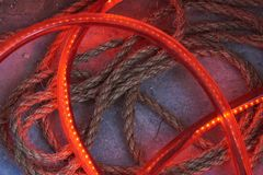 On the floor of concrete are a tube of plastic and a rope. Inside the tube are red LEDs. Background. On the floor of concrete are a tube of plastic and a rope royalty free stock image