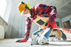 Builder at work. cutting concrete floor for cabling by diamond slitting machine. Floor construction work. Construction worker cutting cement floor topping by stock images