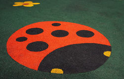 Floor covering children's playground with a ladybug Royalty Free Stock Photos