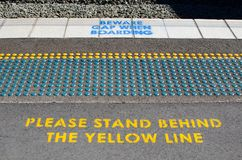Floor Dots to help blind people finding their way and warning signs `Please stand behind the yellow line and beware gap when board. A Floor Dots to help blind royalty free stock images