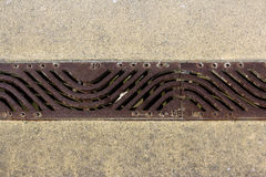 Floor drain. A elongated of stylized floor drain made out of cast iron on the ground with patterns Stock Images