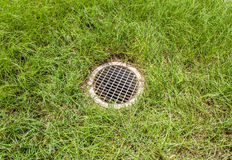 Floor drain contrast with green grass background Royalty Free Stock Photos