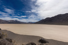 Floor of a dry lake with cracked mud. Floor of a dry Racetrack Playa lake with cracked mud, blue sky, clouds and mountains. Racetrack Playa. Death Valley Royalty Free Stock Images