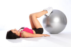 Floor exercise with ball by beautiful woman in gym. Floor exercise by beautiful young woman lying on her back with feet balanced on silver fitness ball. She is royalty free stock photography