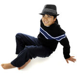 On the Floor with a Fedora. Overhead view of a barefoot, biracial preteen in a charcoal fedora.  On a white background Stock Photos