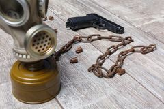 On the floor,are a gas mask is a chain, a pistol and a few raspy cartridges. stock photo