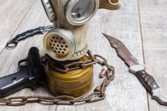 On the floor is a gas mask next to is a pistol and an knife. Royalty Free Stock Image