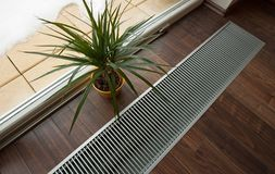 Floor heating. Underfloor heating recessed into the floor near the window Royalty Free Stock Photo