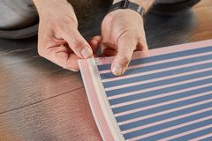 Floor heating installation. Installation infrared carbon heating film for floor. Male hands are fastening the contact clip to heating film roll. Electrical floor royalty free stock image