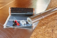 Floor heating installation. Installation infrared carbon heating film for floor. Heating film roll, termostat and roll for termal insulation lies on OSB floor in royalty free stock photography