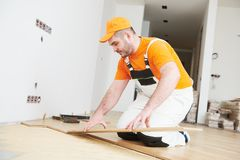 Worker joining parquet floor. Floor installation. carpenter worker installing wood parquet board Royalty Free Stock Image