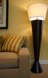 Floor Lamp. Modernistic brown, wooden floor lamp next to sofa and pillow Royalty Free Stock Photo