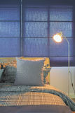 Floor lamp next to comfy bed in night time. At home Royalty Free Stock Photography