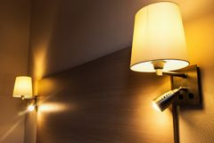 Floor lamp on the wall above the bed in the room Stock Photos