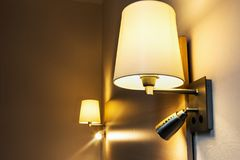 Floor lamp on the wall above the bed in the room Royalty Free Stock Photography