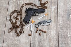 On the floor the layout is from chain, a pistol, ammunition, a knife and several cigarettes. On the wooden floor the layout is from an old rusty chain, a black Stock Photos