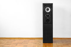 Floor loudspeaker. Single floor-standing loudspeaker on hardwood against white wall Stock Images