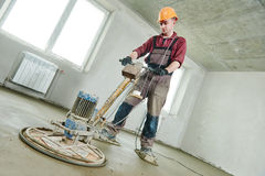 Floor machine grinding by power trowel. Construction worker walk behind power trowel machine during concrete floor wet grinding process by electrical grinder Royalty Free Stock Images