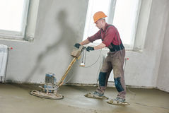 Floor machine grinding by power trowel. Construction worker walk behind power trowel machine during concrete floor wet grinding process by electrical grinder Stock Images