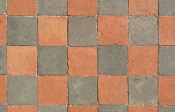 The floor is made of stone of different colors .Texture or background. The floor is laid in a checkerboard pattern of square stone of different colors .Texture stock illustration