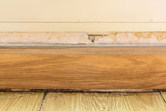 Floor moldings and paint color swelling on old white wall Royalty Free Stock Photos