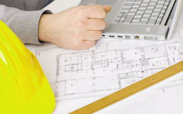 Floor plan on architect's desk. Along with laptop computer, yellow hardhat and ruler Stock Image