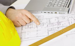 Floor plan on architect's desk. Along with laptop computer, yellow hardhat and ruler Stock Photo