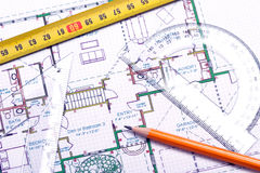 Floor plan and architect's tools. Topview of a tape measure, pencil and other tools on top of floor plan royalty free stock photos
