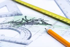 Floor plan and tools. Pencil, tape measure, nails and geometric tools on top of a floor plan. Focus on nails royalty free stock photos