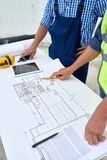 Floor Plans for Construction. Close up of two unrecognizable construction workers discussing floor plans and engineering documentation on site, focus on royalty free stock images