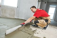 Floor cement work. Plasterer smoothing floor surface with screeder stock image