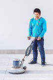 Floor polishing. Asian worker using floor polishing machine in office building royalty free stock photo