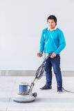 Floor polishing. Asian worker using floor polishing machine in office building royalty free stock photos