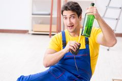 The floor repairman drinking alcohol during break. Floor repairman drinking alcohol during break stock image