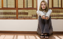 Floor sitting girl. Blond girl sitting in the sun next to the window thinking about the future Royalty Free Stock Images