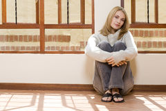 Floor sitting girl. Blond girl sitting in the sun next to the window thinking about the future Stock Photography