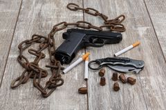 On the floor is an rusty chain, a pistol, a few ammunition and several cigarettes with a filter. On the floor there is an old rusty chain, a black pistol, a few Stock Photos