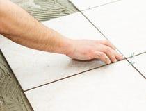 Floor Tiling. Handyman doing renovation works - floor tiling royalty free stock photo