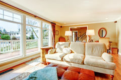 Floor-to-ceiling windows living room with a rustic beige couch. Bright warm colors living room with rustic furniture and floor-to-ceilign windows Stock Image
