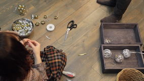 On the floor, two people make ties for Christmas decorations. Around people is a wooden box with silver ornaments, a bowl with yellow balls, empty basket with stock footage
