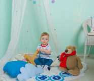 On the floor under the curtain sits and plays with plane boy baby Stock Photos