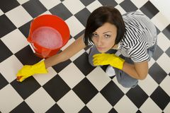 This floor is very dirty. Young woman in yellow rubber gloves scrubs the floor. She's kneeling beside bucket with water. Looking at camera. Whole body. High royalty free stock photo