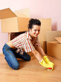 Floor washer. Happy young woman with yellow rubber gloves scrubs the floor Stock Images