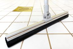 Floor wiper. Cleaning tiled bathroom with floor wiper Stock Photos